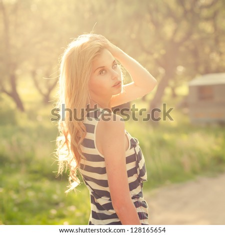 portrait of a beautiful blonde in the summer in the park. Photos in the soft light and warm colors - stock photo