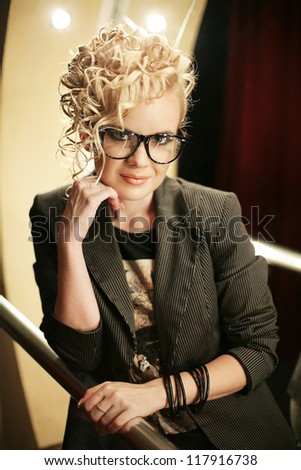 portrait of a beautiful blonde party girl on the stage of the club. Indoor shot - stock photo
