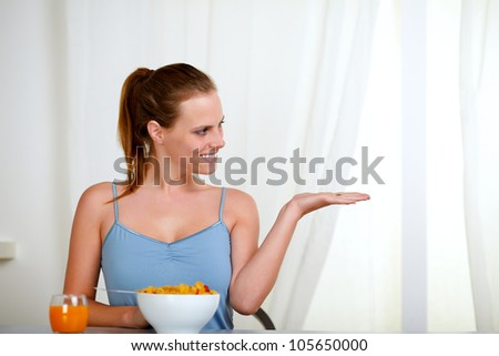 Portrait of a beautiful blonde woman eating healthy breakfast and looking to the right - stock photo