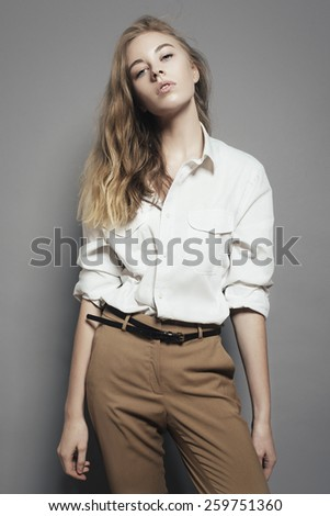 Portrait of a beautiful blonde woman in a white shirt in the studio on a gray background - stock photo
