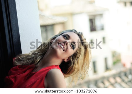Portrait of a beautiful blonde woman in a window wearing a red dress