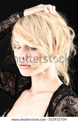 Portrait of a beautiful blonde woman. Studio shot over black background. - stock photo