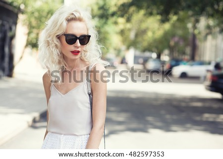 Portrait of a beautiful blonde woman walking outside with sun glasses and red lips.