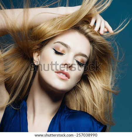 Portrait of a beautiful blonde woman with long hair in a studio on a blue background, the concept of health and beauty - stock photo