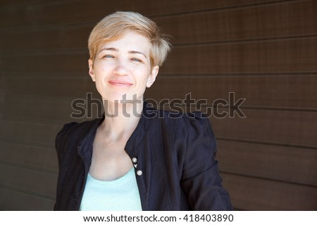 Portrait of a beautiful blonde woman with short hairstyle and casual stylish clothes in her early 40s outdoors in summer. - stock photo