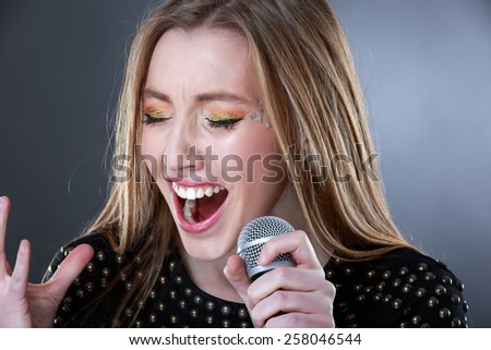 Portrait of a beautiful blonde young woman singing into microphone - stock photo