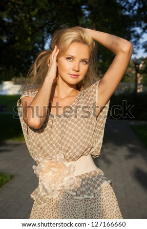 Portrait of a beautiful blonde young woman with blue eyes keeping her hair with hands, in park
