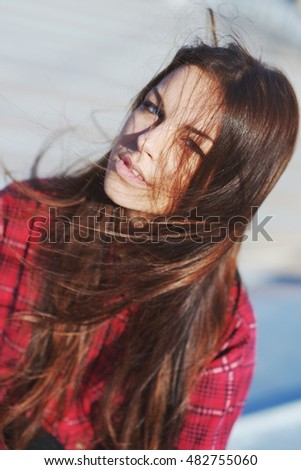 Portrait of a beautiful blue-eyed girl with long silky, disheveled by the wind, with hair in a red plaid shirt. Closeup.