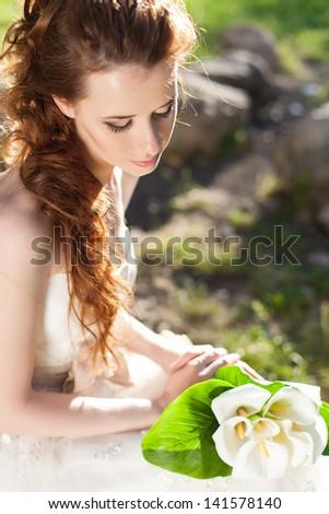 portrait of a beautiful bride in garden posing in her wedding day - stock photo