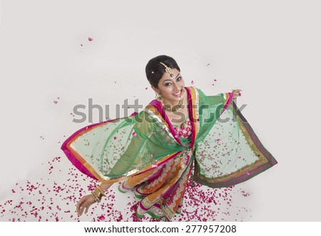 Portrait of a beautiful bride surrounded by rose petals - stock photo
