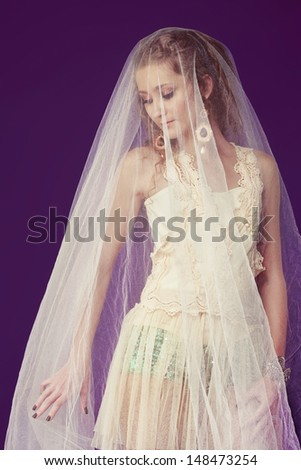Portrait of a beautiful bride with long curly hair wearing lace dress over shorts standing under tulle veil on purple studio background - stock photo