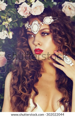 portrait of a beautiful brunet with accessories in the summer garden - stock photo