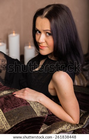 Portrait of a beautiful brunette. Different emotions. Portrait of a girl in a bedroom in chocolate tones. Girl holding an embroidered pillow. The concept of beauty and relaxation. - stock photo