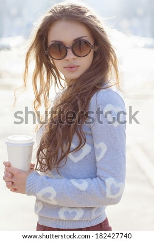 Portrait of a beautiful brunette girl in sunglasses standing on the street. Keeping drink in her hands. Warm sunny day. Outdoors - stock photo
