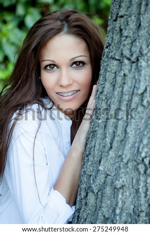 Portrait of a beautiful brunette girl next to a tree - stock photo