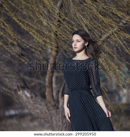 Portrait of a beautiful brunette girl on the nature. Beautiful smiling girl. Brunette hair girl.in black dress outside. European beautiful brunette girl.