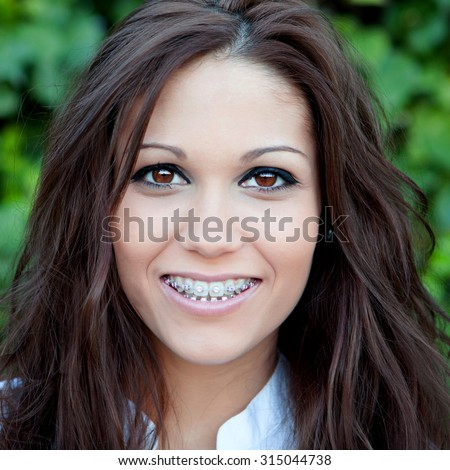 Portrait of a beautiful brunette girl with brackets (braces) outdoors in the park - stock photo