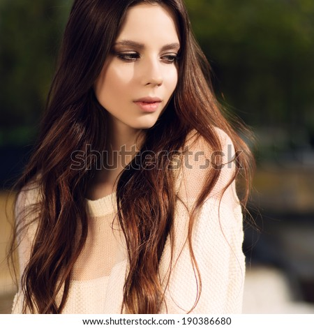 Portrait of a beautiful brunette girl with long hair outdoors - stock photo