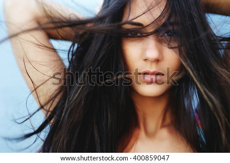 Portrait of a beautiful brunette girl with long hair waving wind