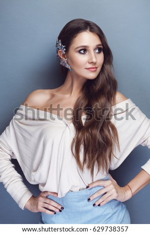 Portrait of a beautiful brunette girl with long wavy hair posing on pastel blue background. There is a gorgeous crystal cuff on her ear.