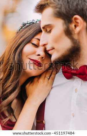Portrait of a beautiful brunette girl with red lips and young stylish man softly embracing close up. Outdoor shot - stock photo