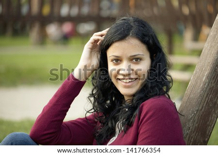 Portrait of a beautiful brunette in the park - stock photo