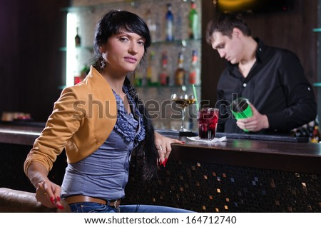 Portrait of a beautiful brunette independent young woman relaxing alone with a cocktail at the bar in a fancy location