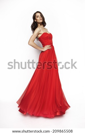 Portrait of a beautiful brunette model in red,long dress posing in studio - stock photo