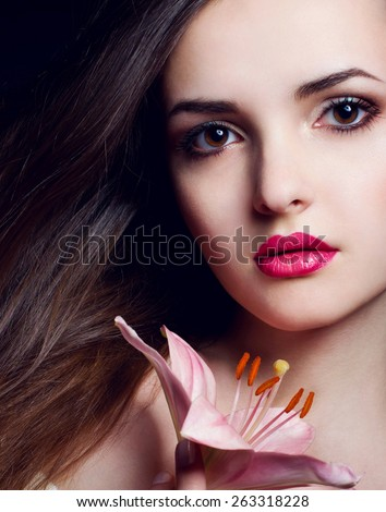 Portrait of a beautiful brunette model woman face with pink flower, lily - stock photo