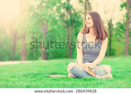 portrait of a beautiful brunette student girl with books on the green grass in the park in spring time.