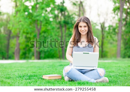 portrait of a beautiful brunette student girl with laptop computer on the green grass in the park in spring time. - stock photo