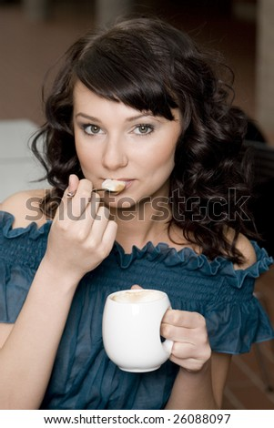 Portrait of a beautiful brunette who is drinking coffee. - stock photo