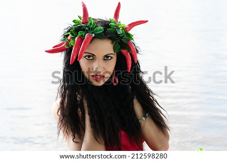 portrait of a beautiful brunette with red pepper on the head - stock photo