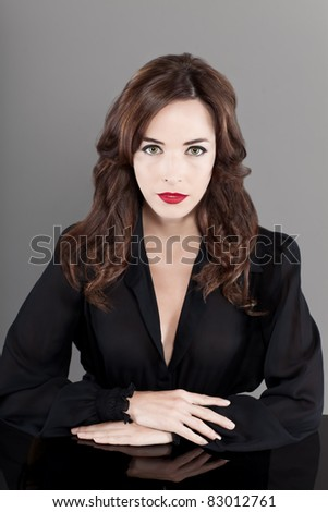 Portrait of a beautiful brunette woman in black casual sitting at table isolated on gray background - stock photo