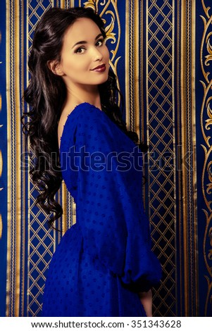 Portrait of a beautiful brunette woman in elegant evening dress posing over vintage background. Fashion shot. Hairstyle. - stock photo