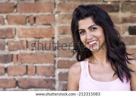 portrait of a beautiful brunette woman on a brick wall background
