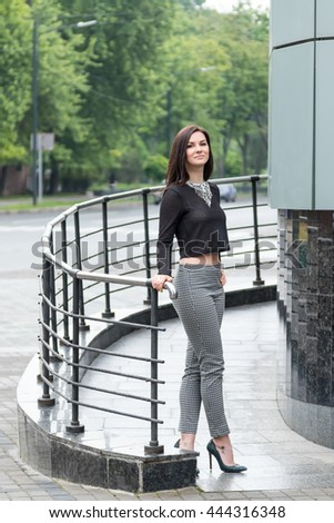 Portrait of a beautiful brunette woman standing near the railing beside the road after rain - stock photo