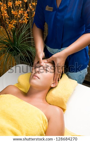 Portrait of a beautiful brunette woman taking head massage - stock photo