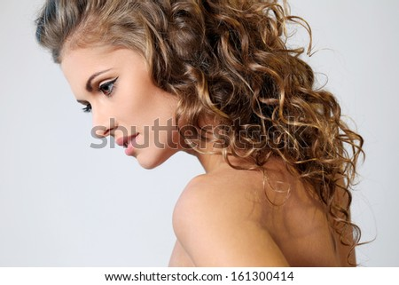 Portrait of a beautiful brunette woman with curly hair and naked shoulders posing over a light background