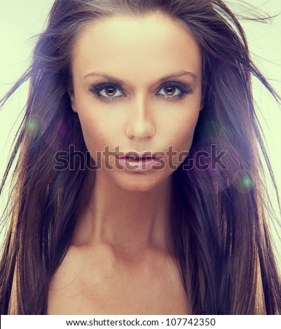 Portrait of a beautiful brunette woman with large brown eyes and lens flare on a white studio background - stock photo
