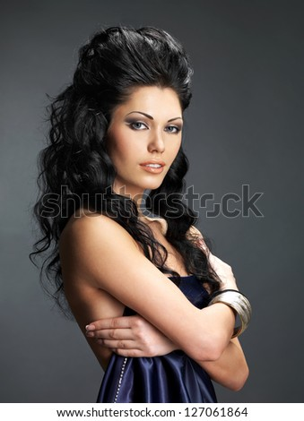 Portrait of a beautiful brunette woman with long creative hairstyle.  Fashion model posing at studio. - stock photo