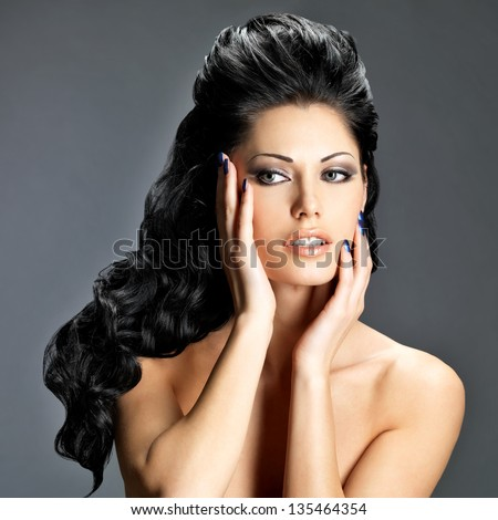 Portrait of a beautiful brunette woman with long creative hairstyle.  Fashion model posing at studio.