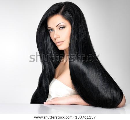 Chân dung của một người phụ nữ tóc nâu xinh đẹp với mái tóc thẳng dài đặt ra ở trên nền màu xám