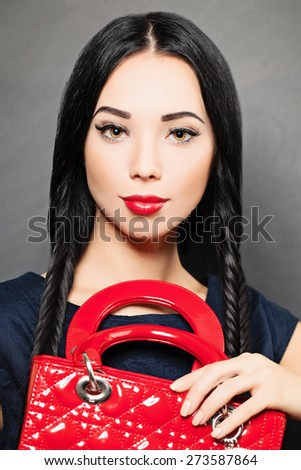 Portrait of a beautiful brunette woman with red handbag in her hand. Fashion photo - stock photo