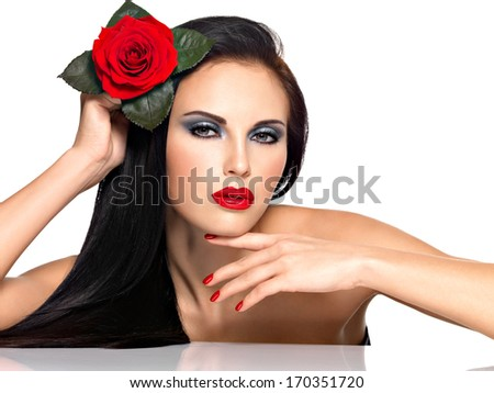 Portrait of a beautiful brunette woman with red nails and lips holds the red rose - stock photo