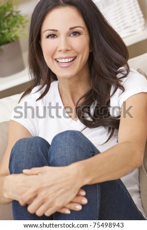 Portrait of a beautiful brunette young woman in jeans and t-shirt smiling siting on her sofa at home - stock photo