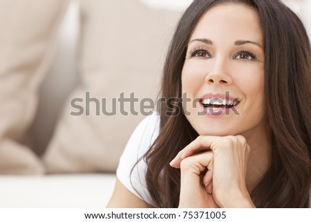 Portrait of a beautiful brunette young woman in t-shirt smiling laying on her sofa at home - stock photo