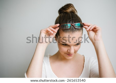 Portrait of a beautiful brunette young woman with clear skin putting reading glasses on, white background - stock photo