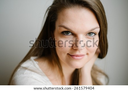 Portrait of a beautiful brunette young woman with clear skin, white background - stock photo