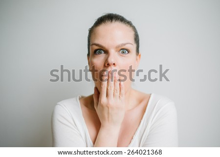 Portrait of a beautiful brunette young woman with expression of surprise, white background - stock photo
